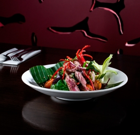 Thai beef stir fry salad on restaurant dark shiny table with red background wall