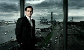 Moody portrait of engineer in front of window view of docklands