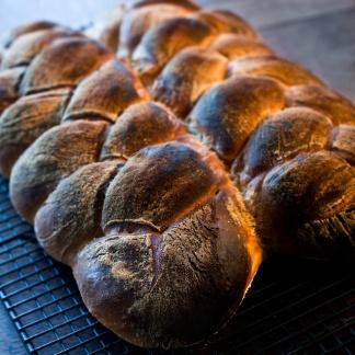 Kosher or twisted bread on steel baking rack in daylight kitchen