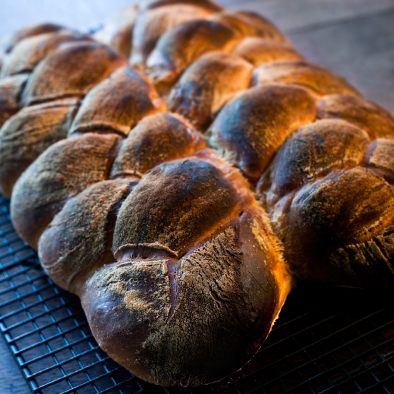 Kosher or twisted bread on steel baking rack in daylight kitchen