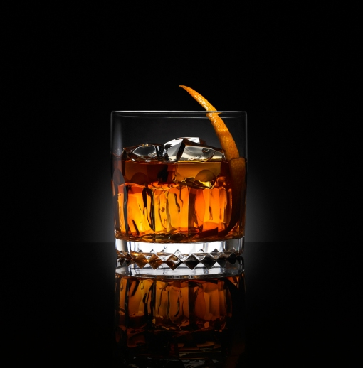 Old fashioned cocktail in cut glass tumbler on black reflective background
