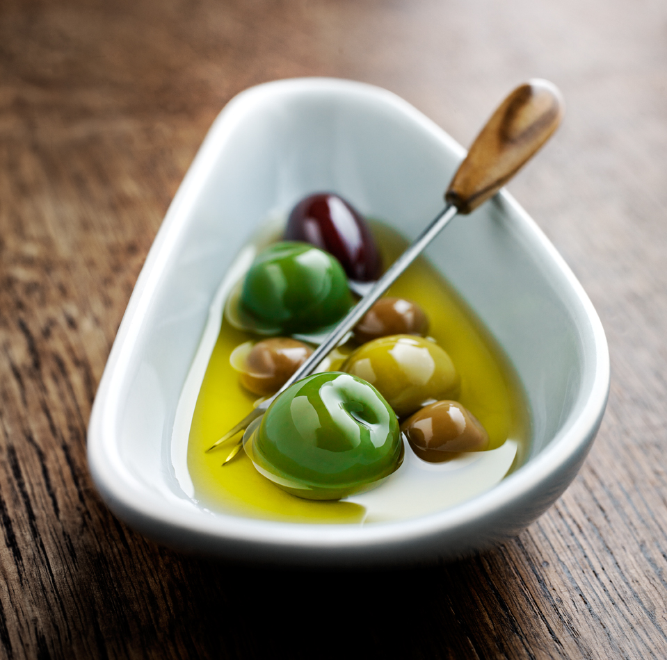 Green olives in white oval dish on wooden table with wooden olive pick