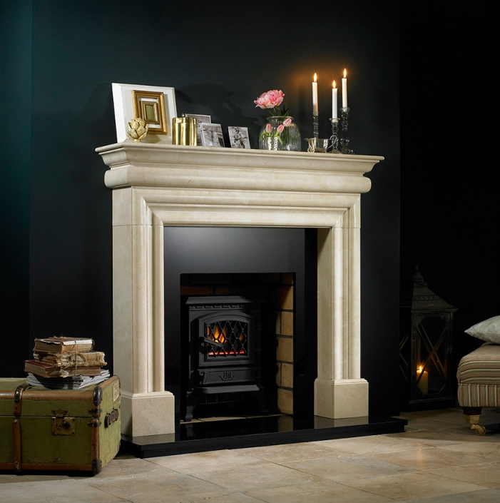 Traditional light granite fireplace with antique props in living room with candle light