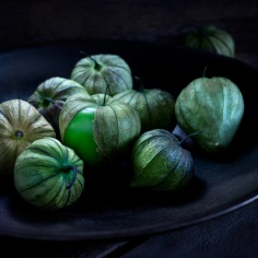 Tomatillos in rustic steel bowl on wooden table